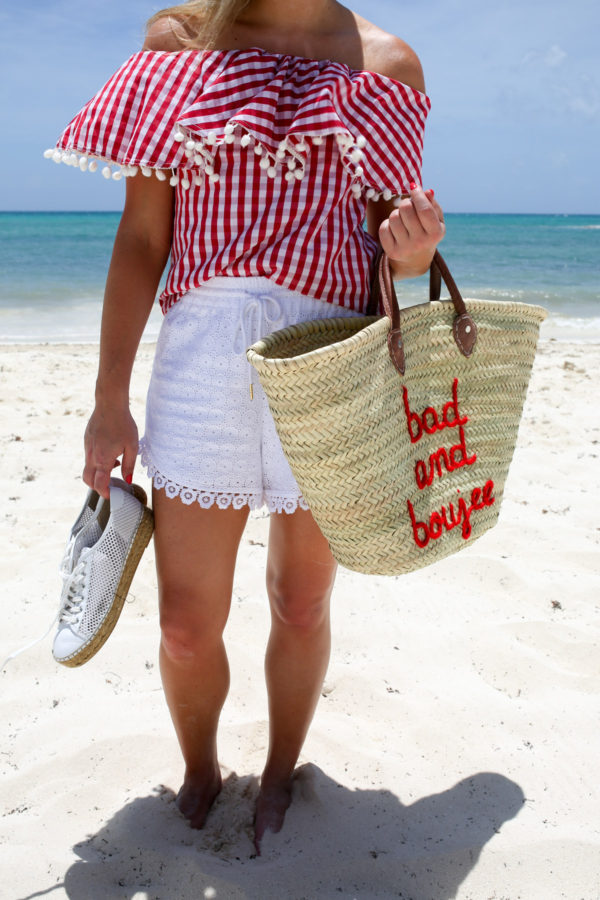 Bows & Sequins styling a red and white summer outfit with a red gingham off the shoulder top and white shorts, with a straw tote.