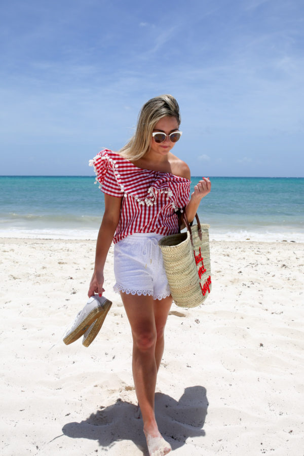 Bows & Sequins wearing a red gingham off the shoulder top with white lace shorts and a straw tote.