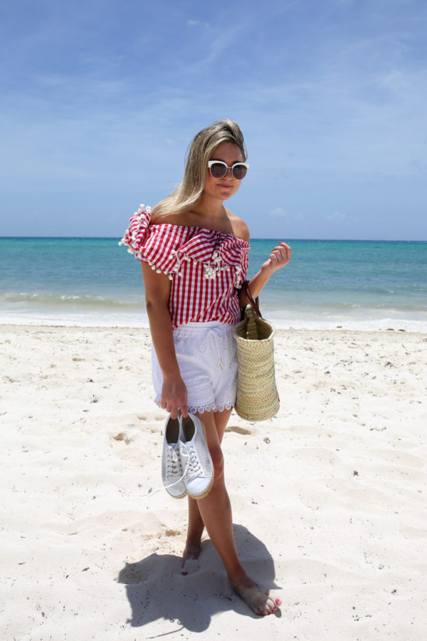 Bows & Sequins wearing a red gingham pom pom hem top with white shorts and a straw tote at the Fairmont Mayakoba resort in Mexico.