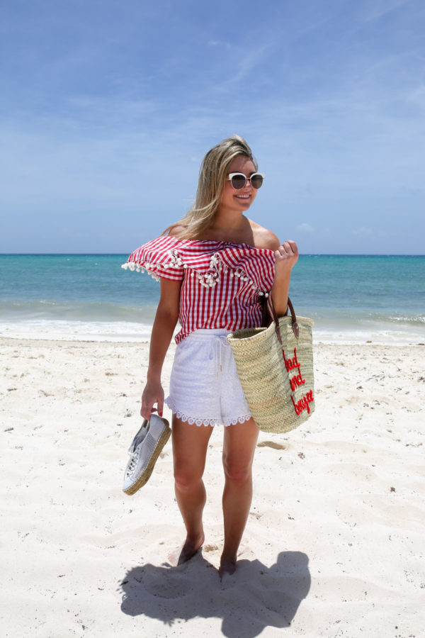 Travel writer Bows & Sequins wearing a red gingham pom pom top with a Bad and Boujee straw tote on the beach in Mexico.