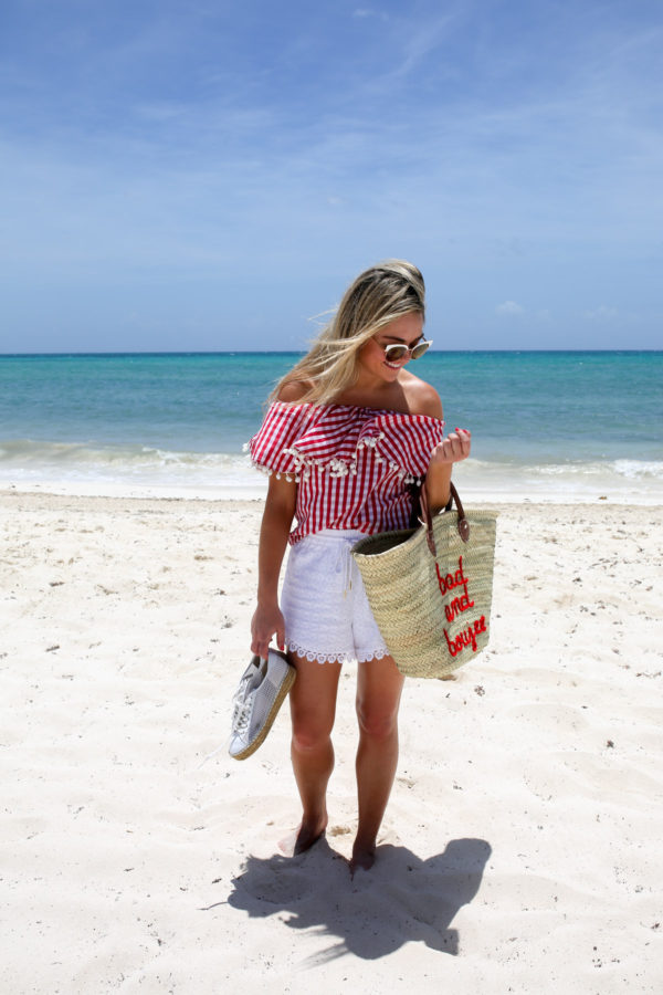 Jessica of Bows & Sequins, a fashion-focused lifestyle blog, wearing white lace shorts and a red gingham off the shoulder top with a straw tote at the Fairmont Mayakoba resort in Mexico.
