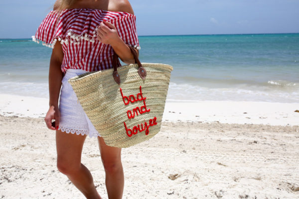 Bows & Sequins wearing a gingham pom pom hem off the shoulder top and white eyelet shorts with a Bad and Boujee straw tote in Mexico.