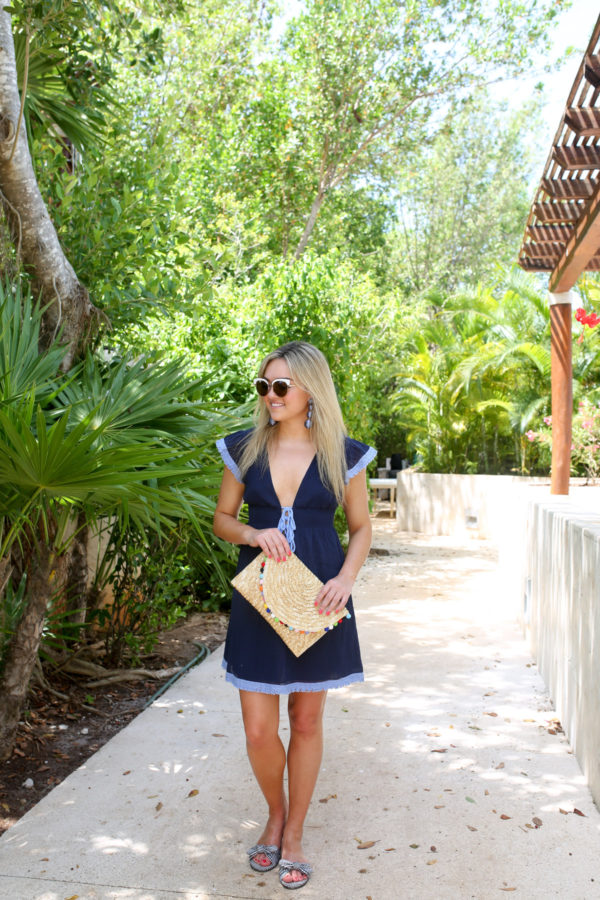 Travel writer Jessica of Bows & Sequins wearing a navy bathing suit coverup with a neutral pom pom clutch and gingham bow slides in Mexico.