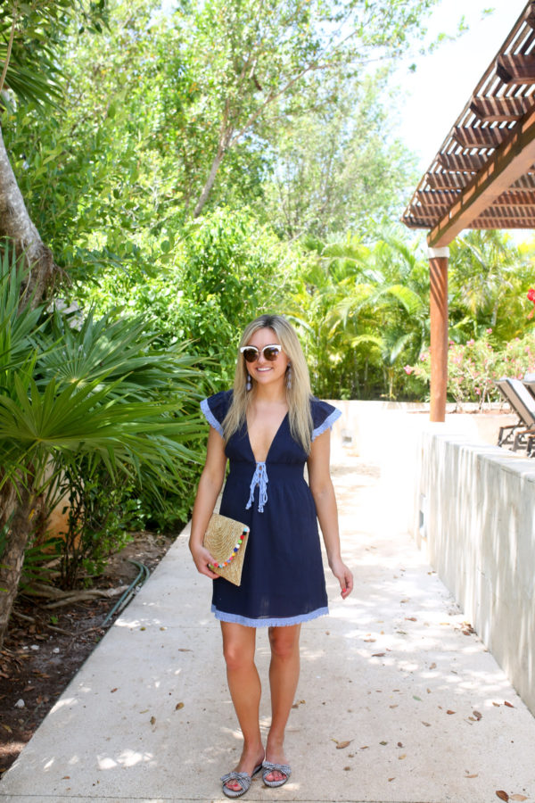 Fashion and lifestyle blogger Bows & Sequins wearing a tie front navy coverup with gingham bow slides and a pom pom clutch at the Fairmont Mayakoba resort in Mexico.