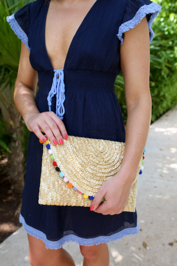 Fashion and lifestyle writer Bows & Sequins holding a neutral pom pom clutch and wearing a Sail to Sable navy cover up.