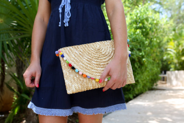 Bows & Sequins styling a navy Sail to Sable bathing suit cover up with a pom pom clutch at the Fairmont Mayakoba resort in Mexico.