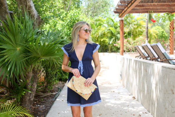 Chicago-based travel blogger Bows & Sequins wearing a navy resort cover up from Sail to Sable with an Alice & Wonder pom pom clutch at the Fairmont Mayakoba in Mexico.