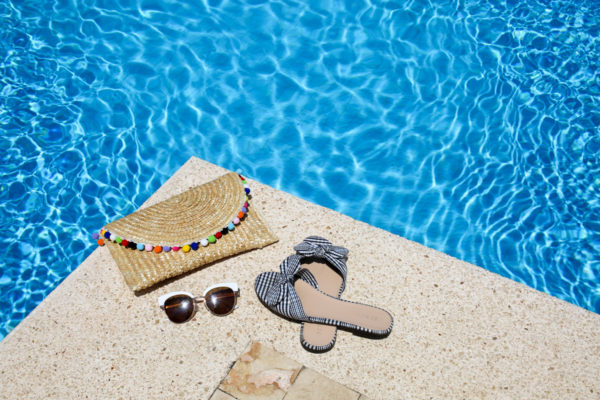 Bows & Sequins shares her pool must haves: an Alice & Wonder pom pom clutch, gingham bow slides, sunglasses