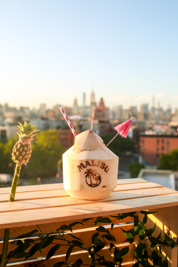 A Malibu coconut cocktail at Tiki Tabu in the LES with a view of the NYC skyline and Empire State Building