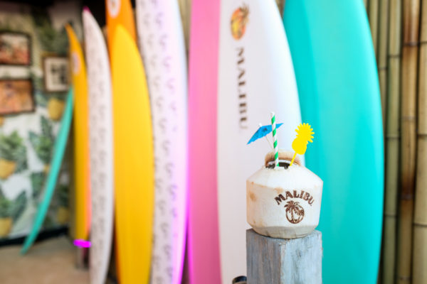 Colorful surf boards and a coconut cocktail by Malibu Rum at the summer kick off party in NYC at Tiki Tabu
