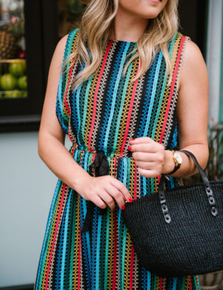 Chicago blogger Bows & Sequins wearing a rainbow striped Eva Franco dress from Anthropologie with a Clare V black straw tote.