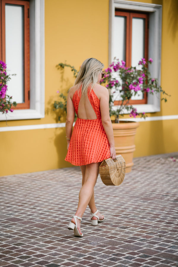 Bows & Sequins wearing a backless orange dress with summer sandals and a bamboo bag at the Fairmont Mayakoba in Mexico.