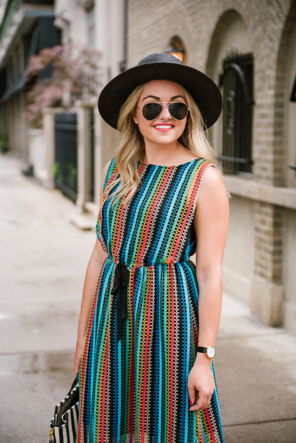 Bows & Sequins wearing a rainbow crochet dress with a black straw hat and aviators.
