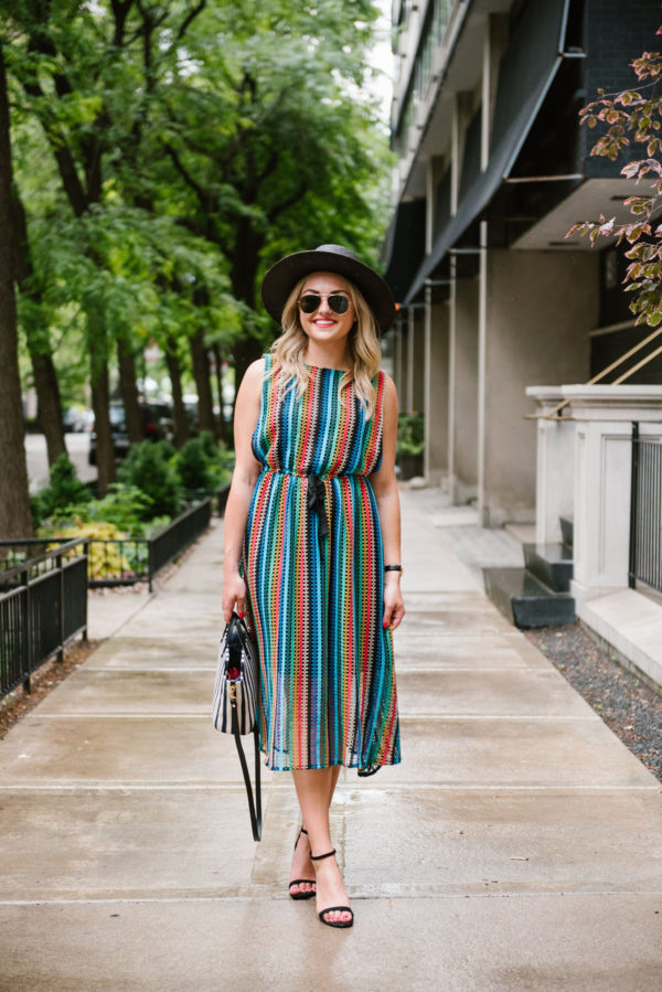 Travel writer Bows & Sequins wearing a rainbow striped Eva Franco dress from Anthropologie with a black straw hat and sandals.