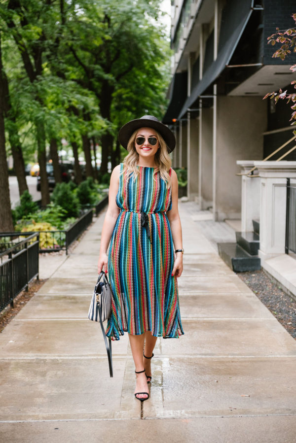 Bows & Sequins styling a rainbow striped midi dress with black sandals, aviators, and a black straw hat.