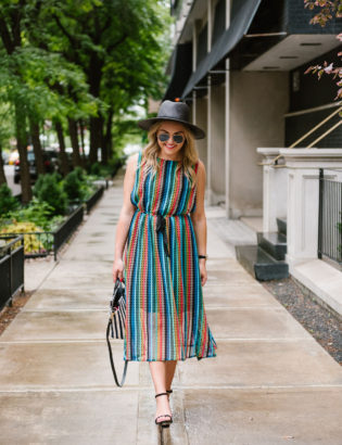 Bows & Sequins wearing an Eva Franco midi dress with black sandals and a Clare V striped bag.