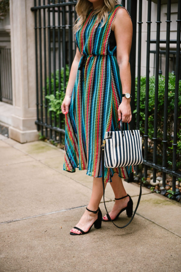 Jessica of Bows & Sequins, a fashion-focused lifestyle blog, wearing a rainbow striped crochet dress, a navy striped bag, and black sandals.