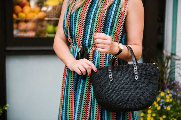 Chicago lifestyle blogger Bows & Sequins wearing an Anthropologie striped dress and a Clare V black straw bag.