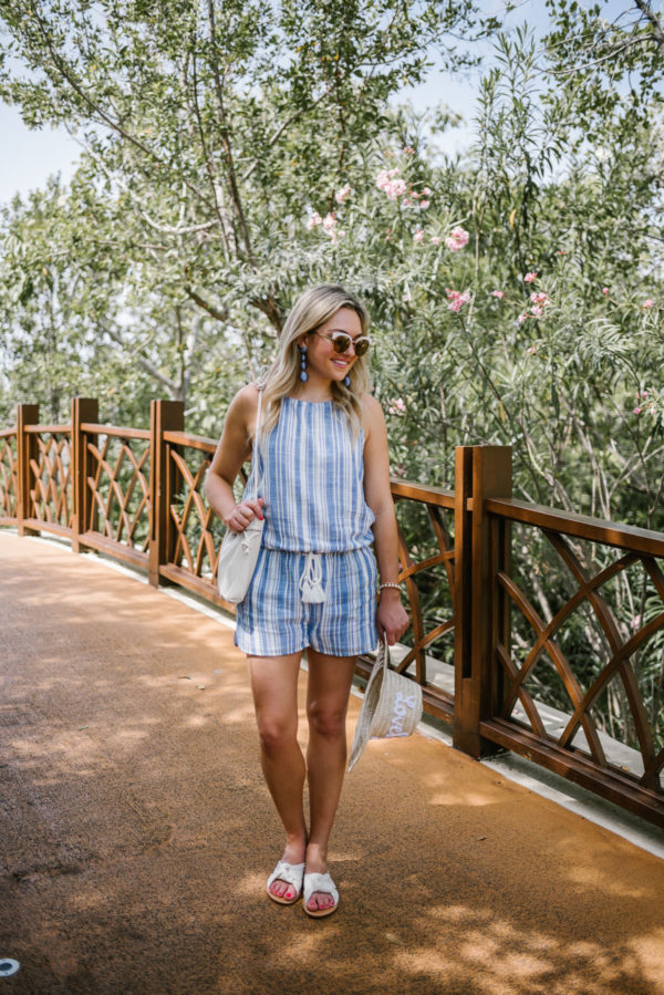 Fashion blogger Bows & Sequins wearing a blue and white Vineyard Vines romper with white Soludos knotted slides and a Clare V Petit Henri bucket bag.