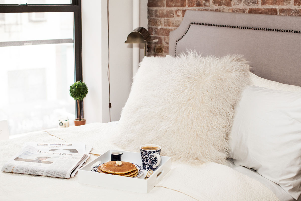 Lifestyle blogger Bows & Sequins with a breakfast in bed setup in her Lower East Side apartment in NYC