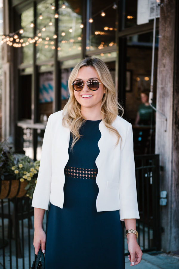 Chicago lifestyle blogger Bows & Sequins wearing a white scalloped Draper James blazer and a navy Sail to Sable dress for work.