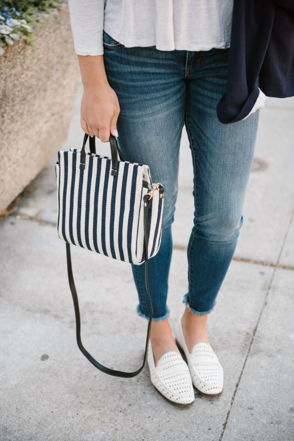 Bows & Sequins wearing Kut from the Cloth raw hem skinny jeans and Sam Edelman woven leather loafers, holding a Clare V striped crossbody bag.