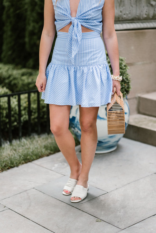 Lifestyle blogger Bows & Sequins styling a matching blue pinstriped crop top and drop waist skirt with white leather slides and a bamboo handbag for summer.
