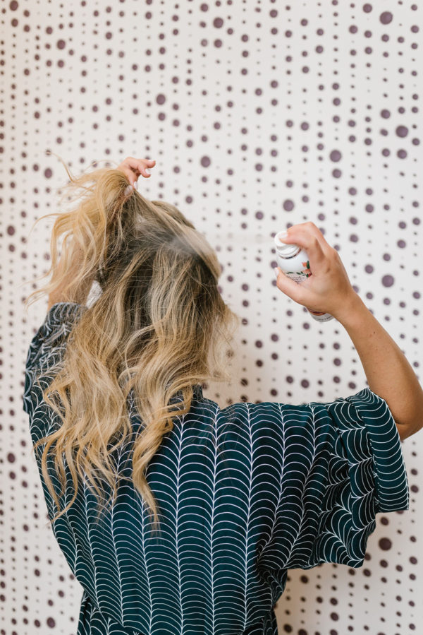Blonde using dry shampoo spray.