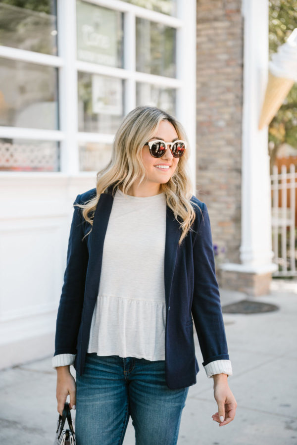 Jessica of Bows & Sequins, a Chicago lifestyle blog, styling a navy Express knit blazer and Old Navy ruffle peplum tee with Illesteva sunglasses.
