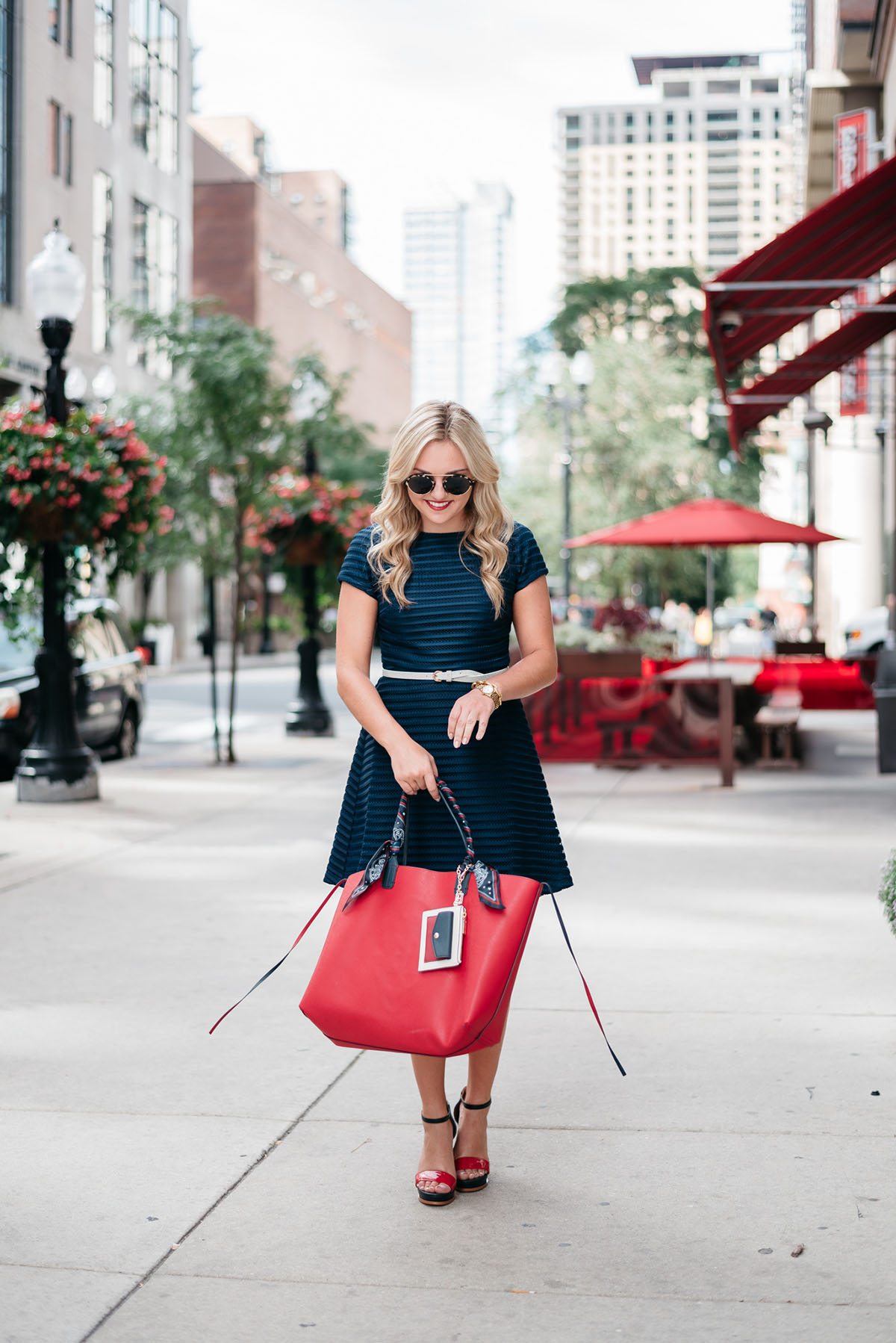 Bows & Sequins holding a Gigi x Tommy collaboration red reversible tote and wearing a navy fit and flare dress.