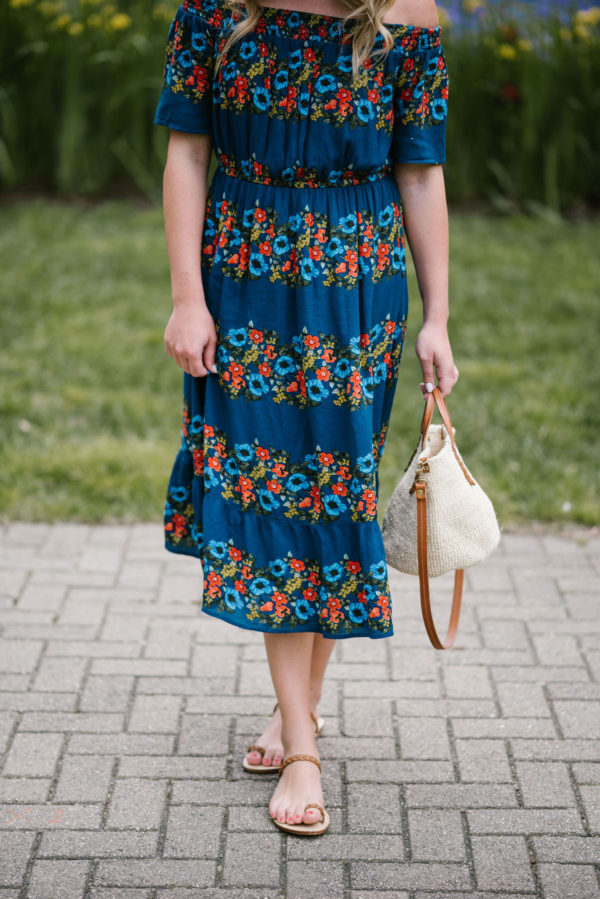Bows & Sequins styling handmade Italian sandals and a floral summer dress with a straw handbag.