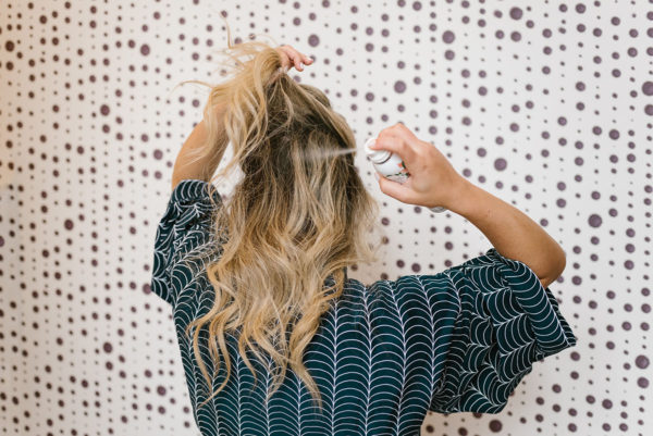 Blonde demonstrating how to use dry shampoo spray in her hair.