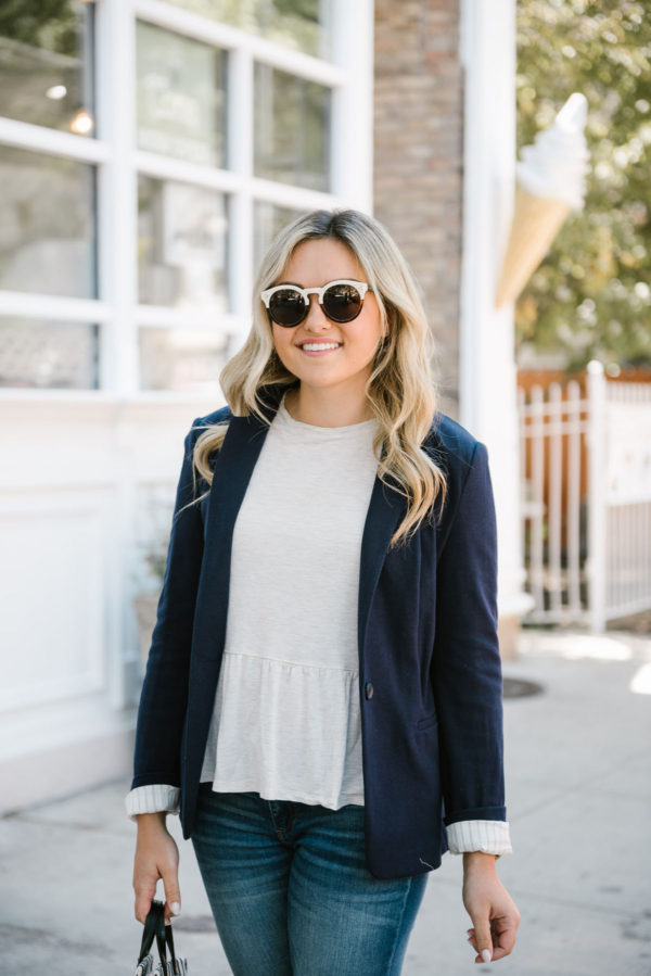 Jessica of Bows & Sequins, a Chicago based fashion-focused blog, wearing Illesteva sunglasses, a navy Express knit blazer, and an Old Navy peplum ruffle tee.