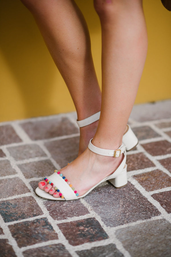 Jessica of Bows & Sequins wearing J.Crew colorful pom pom sandals.