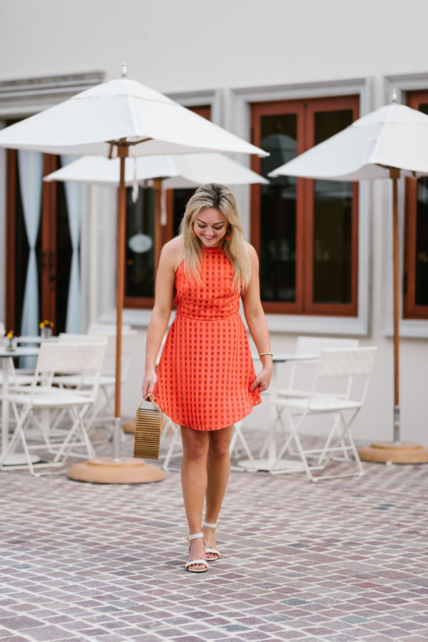 Chicago fashion blogger Bows & Sequins wearing a Lovers + Friends orange dress and J.Crew pom pom sandals at the Fairmont Mayakoba resort in Mexico.