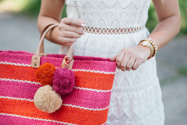 Bows & Sequins holding a Mar y Sol pink and orange stripe pom pom tote and wearing a gold watch and pearl cuff bracelet.