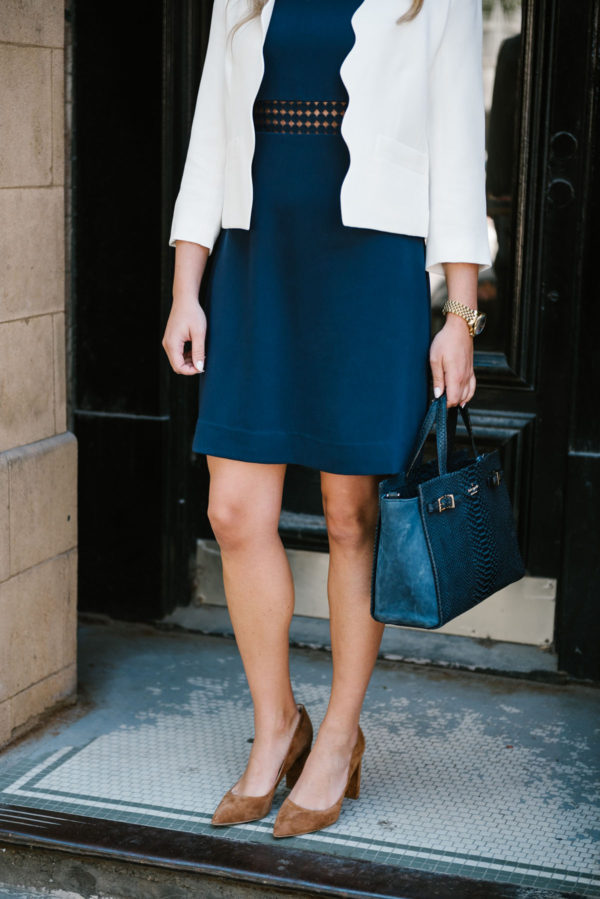 Bows & Sequins wearing a scalloped blazer, a navy Sail to Sable dress, and brown suede pumps, holding a navy Kate Spade handbag.