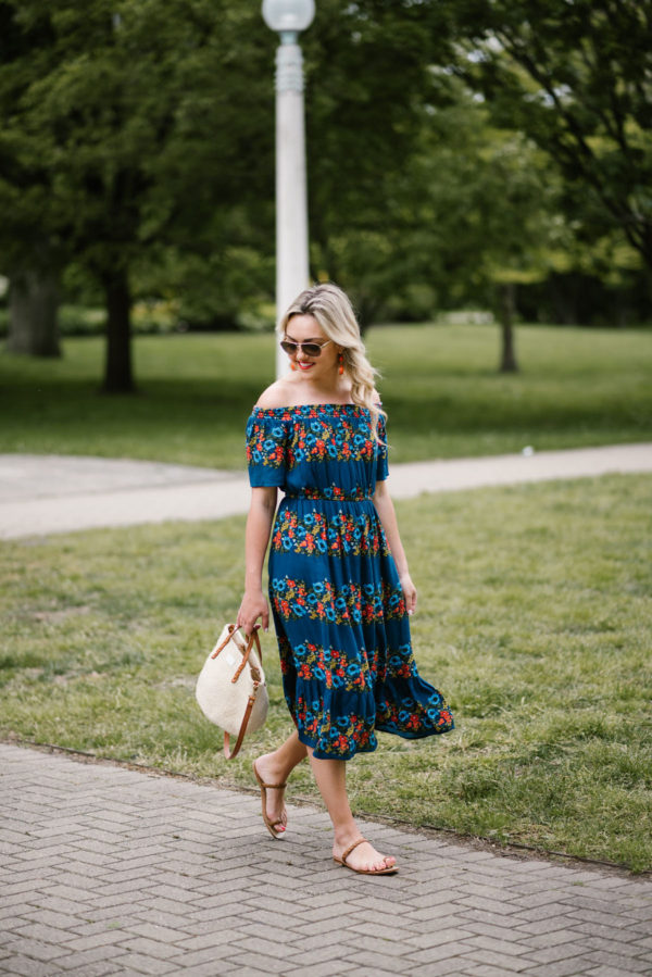 Travel blogger Jessica Sturdy wearing an off the shoulder Old Navy dress, handmade Italian sandals, Ralph Lauren aviator sunglasses, and a Clare V straw handbag.