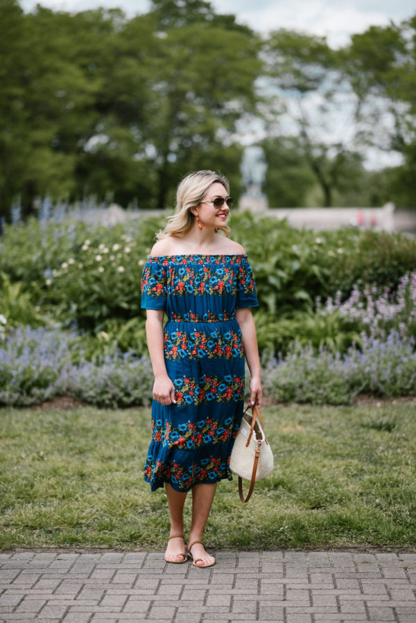 Chicago fashion blogger Bows & Sequins wearing an off the shoulder floral dress with a straw handbag, aviators, and strappy leather sandals.
