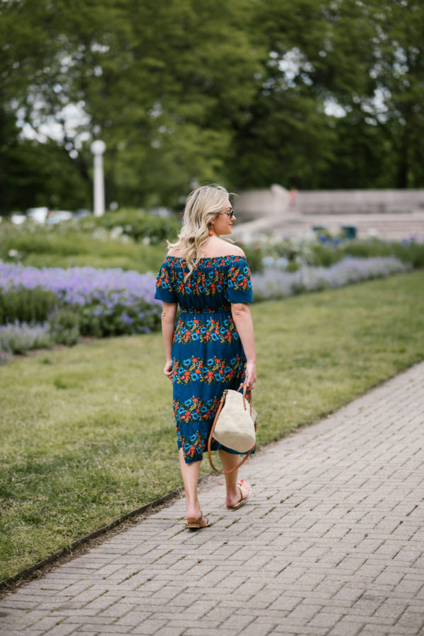 Bows & Sequins wearing an off the shoulder Old Navy floral dress with a straw handbag for summer.