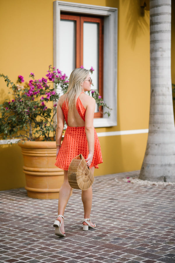 Jessica Sturdy of Bows & Sequins, a Chicago-based lifestyle blog, wearing a backless orange dress with a bamboo handbag at a hotel in Mexico.