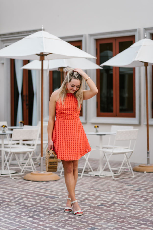 Travel writer Jessica Sturdy styling a Lovers + Friends orange dress with J.Crew pom pom sandals, orange statement earrings, and a Cult Gaia natural bamboo bag.