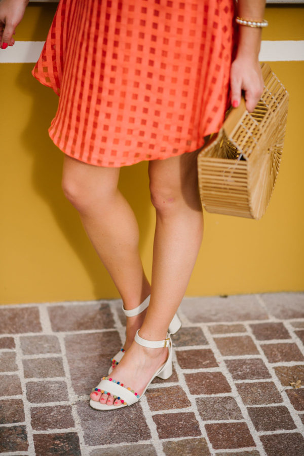 Bows & Sequins wearing an orange summer dress and J.Crew pom pom sandals with a pearl cuff and a Cult Gaia bamboo bag.