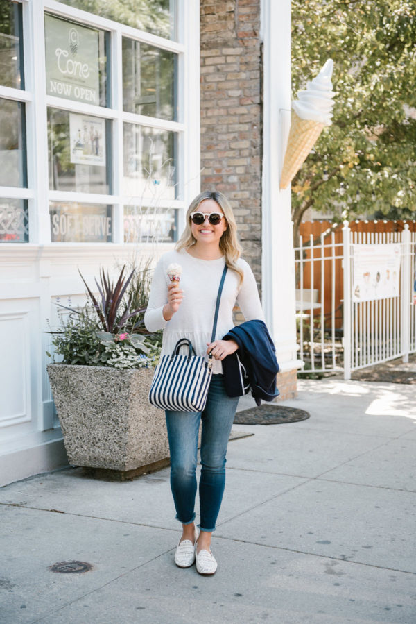 Bows & Sequins, a Chicago based lifestyle blogger, wearing Kut from the Cloth raw hem skinny jeans, an Old Navy ruffle peplum tee, and a Clare V striped crossbody bag.