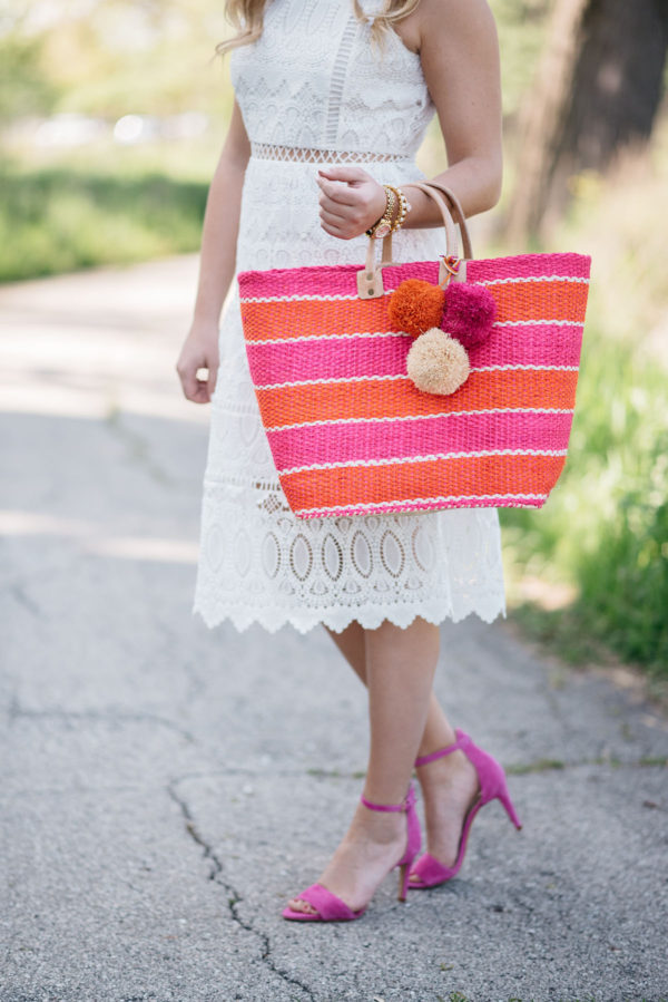 Bows & Sequins wearing a white lace dress and pink sandals, holding a pink & orange pom pom tote.