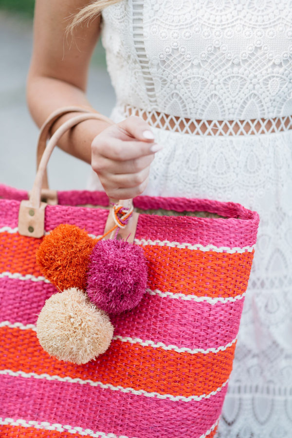 Bows & Sequins holding a pink and orange pom pom straw tote from Mar y Sol.