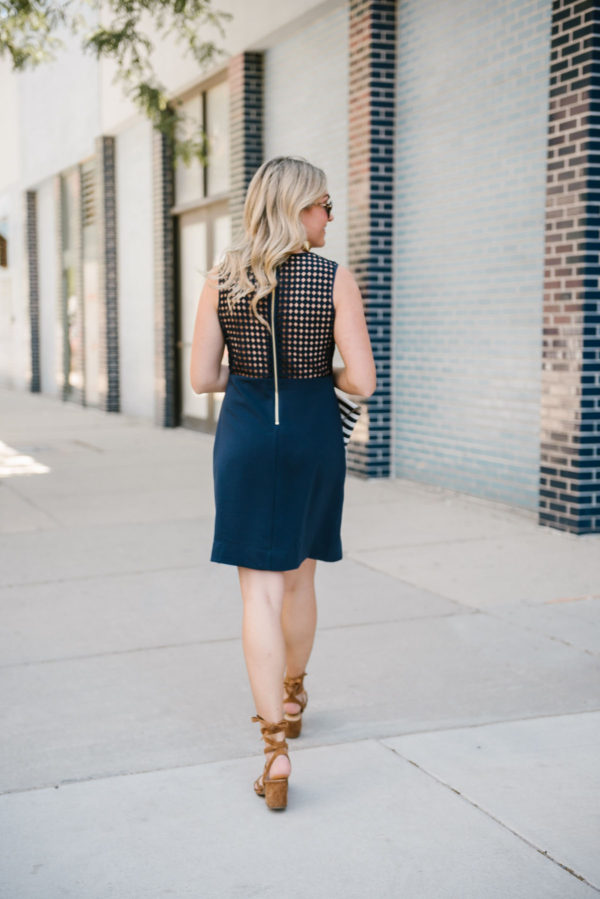 Bows & Sequins wearing a backless navy dress with block heel sandals in Chicago.