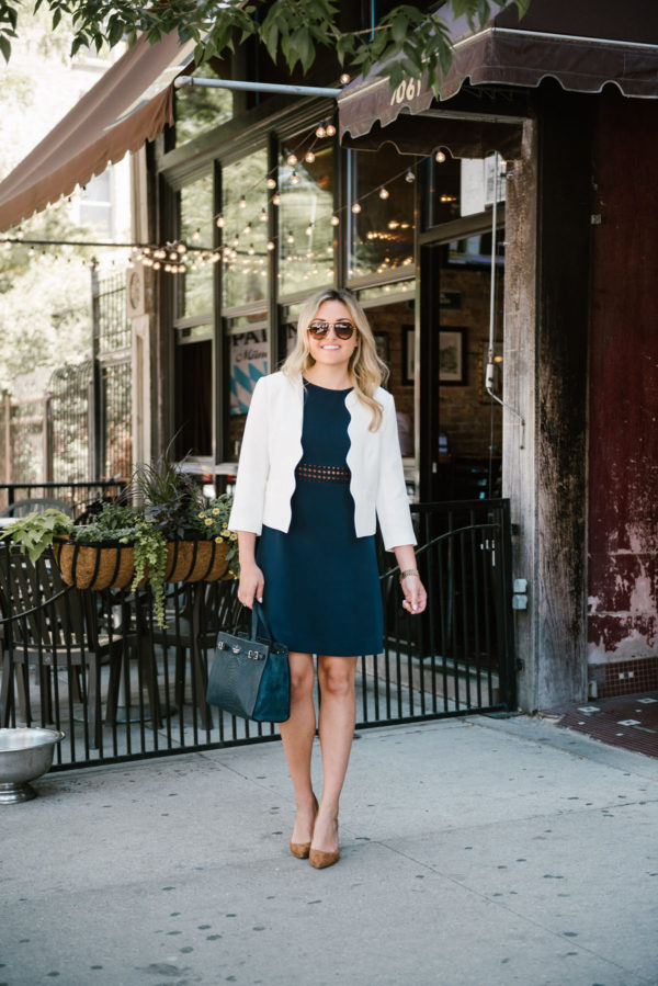 Jessica Sturdy of Bows & Sequins, a Chicago lifestyle blog, wearing a navy dress, a white scalloped blazer, tortoise aviators, and a navy handbag.