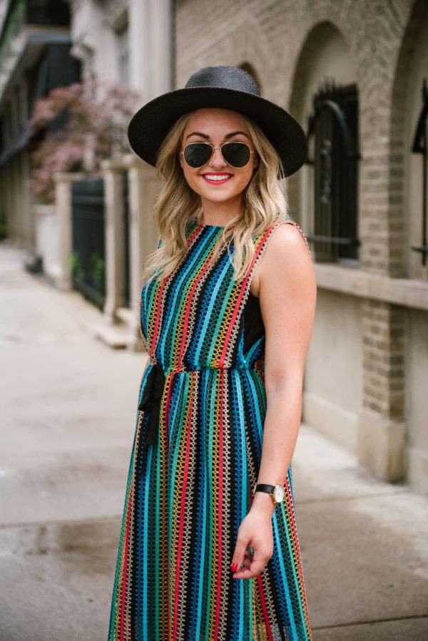 Bows & Sequins, a travel lifestyle blogger, wearing an Eva Franco rainbow striped dress from Anthropologie with a black straw hat for summer.