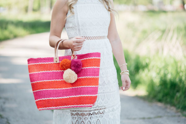 Bows & Sequins holding a pink and orange pom pom straw tote from Mar y Sol and wearing a gold watch and pearl cuff bracelet.